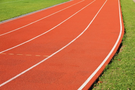 beetwen: Curve of the red running track beetwen green grass
