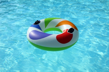 colorfull swim ring floating on a blue swimming pool photo