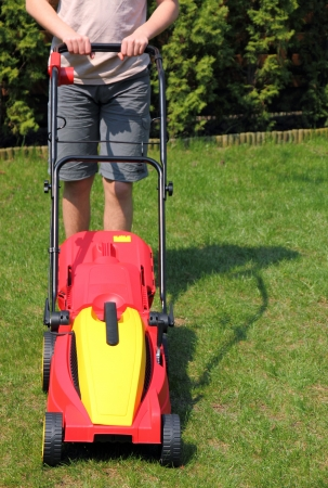 Young man mowing yard with lawnmower photo
