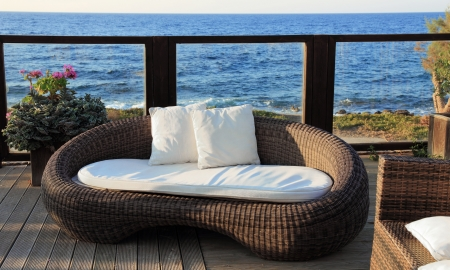 A modern wicker garden sofa in the terrace with sea view Archivio Fotografico