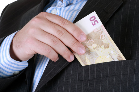 man in suite: Business man hiding money in pocket.