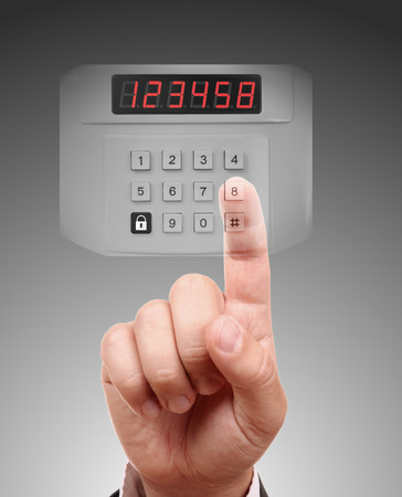 transparent system: Hand is setting home security alarm system Stock Photo