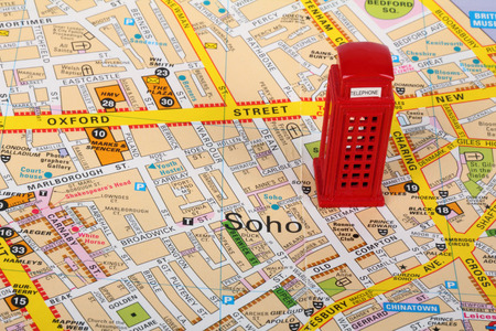 Small model of a red phone box  on top of a map of London photo