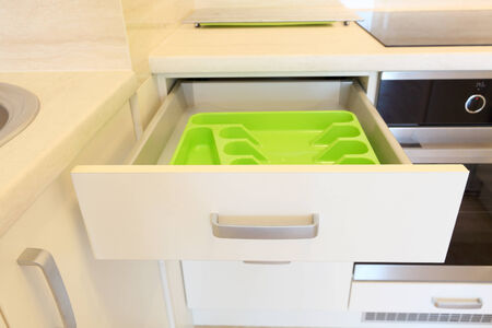 drawers: Empty green plastic cutlery tray in kitchen drawer Stock Photo