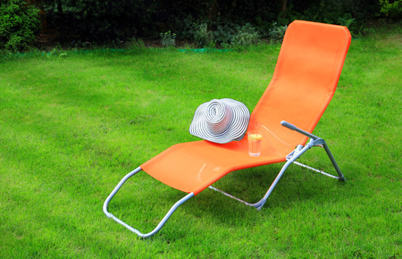 sunbed: orange lounge sunbed standing on green grass in a private green garden