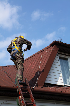 Construction worker wearing safety harness and safety line working on a roof photo