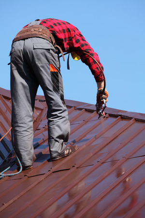 roof work: roofer builder worker with pulverizer spraying paint on metal sheet roof