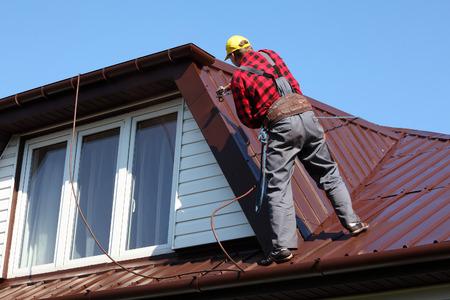 金属シートの屋根の上の塗料の噴霧の粉砕機と屋根葺き職人ビルダー ワーカー