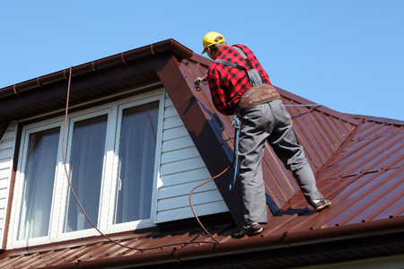 red metal: roofer builder worker with pulverizer spraying paint on metal sheet roof