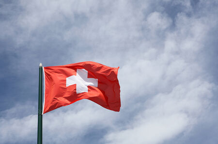 swiss culture: Flag of Switzerland on a sky and clouds