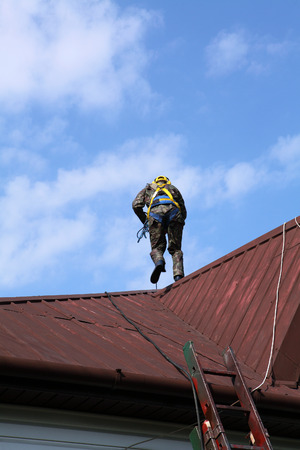 damaged roof: Construction worker wearing safety harness and safety line working on a roof