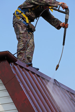 Worker on top of roof, with high pressure washer, cleans layer of old roof