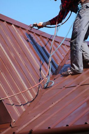 roofer builder worker with pulverizer spraying paint on metal sheet roof