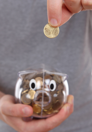 specifically: Male hand putting coin into a piggy bank, focus specifically on the coin Stock Photo