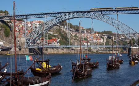 Porto,Portugal - old Portuguese boat on Douro river in front of the Dom Luis I bridge.