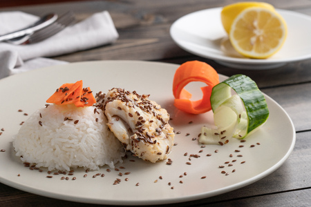 Fish dinner served on white plate and wood table