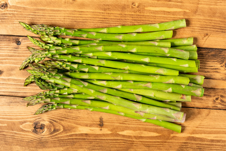 Bundle of asparagus overhead on wooden table
