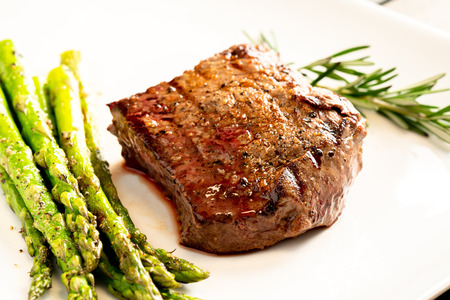 Cooked steak and asparagus served on white plate
