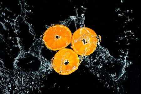 Oranges Water Splash on black background