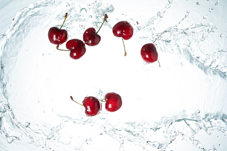 Freeze Motion cherries water splash on white background
