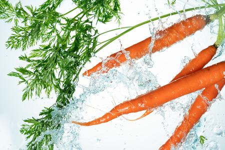 Bunch of orange carrots water splash on white background