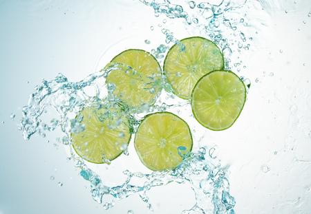 Freeze Motion Limes Water Splash on white background Imagens