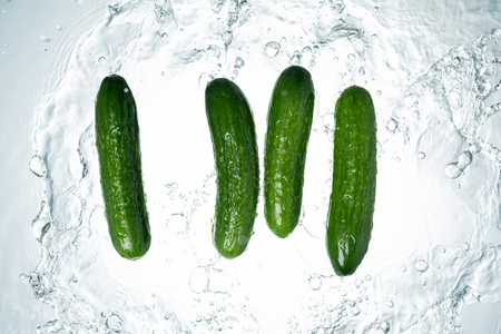 Cucumbers Water Splash on white background Imagens