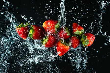 Strawberries Water Splash on black background Imagens