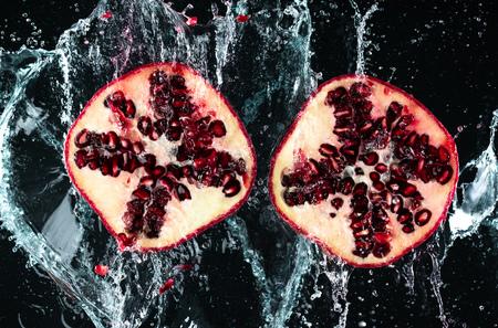 Pomegranate Water Splash on Black Background Imagens