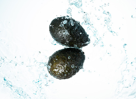 Two Whole Avocados Water Splash on white background
