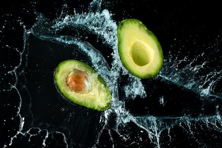 Avocado Water Splash on black background Imagens