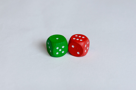 A green and a red colored are isolated. The red one is showing six pips and the green one only one. Stock Photo