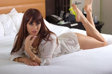 Sexy brunette laying on bed with legs up photo