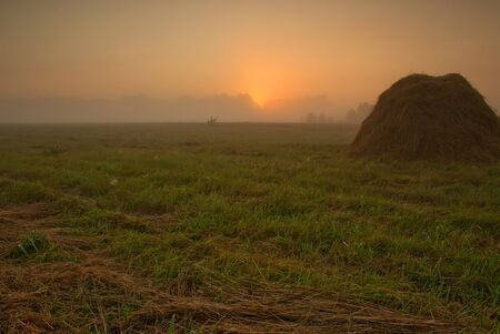 narew: Poland, late summer.Dawn above meadows in the vicinity of the Narew river.On the foreground the one can see the mound of the cut grass and in the background of the fog and the glow of the rising sun Stock Photo