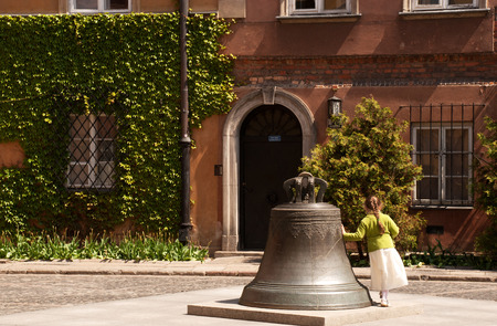 legend: Poland.Warsaw Old town. Bell in the Kanonia Square,legend said if you circle it 3 times will bring you good lucks. girl goes around the bell.Photo was taken in May 2007