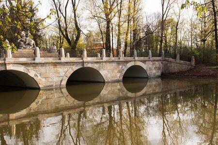 Polonia: Poland,Warsaw.Lazienki Royal park.View on the arcade bridge with  the statue of King John III Sobieski in the background.Photo was taken in April 2015.Horizontal view.