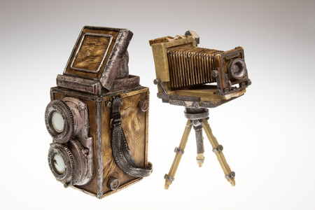 Two old camerasmodels for collectors.Two SLR camera lenses and bellows camera on a tripod.Models made of plaster and leather.Cameras on white isolated background.Horizontal view.
