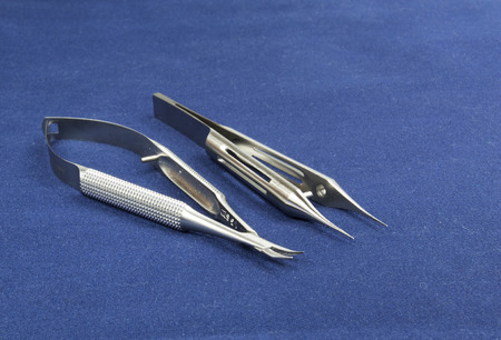 sidelong: Two microsurgical instruments on blue background , sidelong view.Scissors,soft curve and forceps with platform