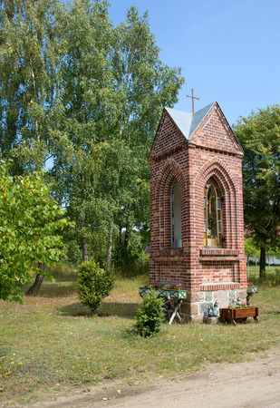 chappel: Poland in summer.Pomerania.Roadside chapel in the countryside.Very often found in rural areas sacral building.Vertical view Stock Photo