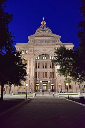 senators: Austin.Texas in United States of America - August 2015.Texas parliament building in the evening, the illuminated front.At the top of the building waving two flags: American and Texas.Editorial.Horizontal view.