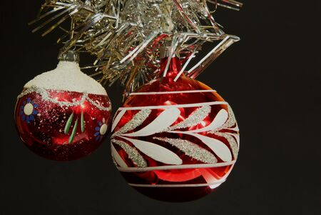 imposed: Two red Christmas balls with ornaments of imposed from the top of an ornate silver chain. The whole on a black isolated background Stock Photo