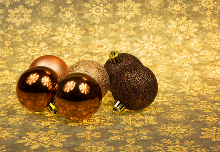 Five Christmas baubles ln a group on the Christmas brownish-yellow stars background.Horizontal view.