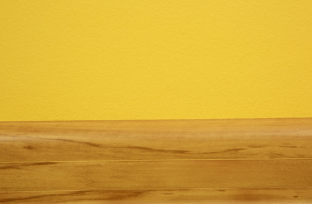 yellow alder: Wooden skirting board in the color of light alder, connecting the yellow wall with floor.Close,horizontal view.