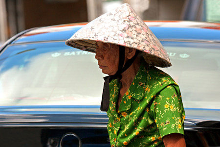 conical hat: Little India,Singapore-March 2008.The old Chinese woman in traditional conical hat , walkin on the street in Little India district in Singapore,March 2008.Editorial.Horizontal view,