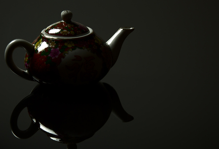 mistic: Chinese jug with a mirror image, on a black background with light reflections. Close horizontal view. Stock Photo