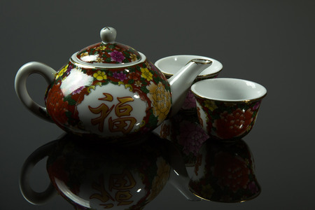 mirro: Chinese jug and two cups with a clear mirror reflection, isolated against a dark gray tle.Close horizontal view.