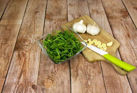 hojas antiguas: rúcula hojas frescas en un recipiente de vidrio, dos cabezas de ajo, ajo picado y un cuchillo en una vieja encimera de madera en tablones viejos de madera marrón