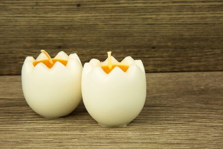 two and a half: Two white candles in the shape of half an egg, Easter decoration on an old wooden table. Close, horizontal view.