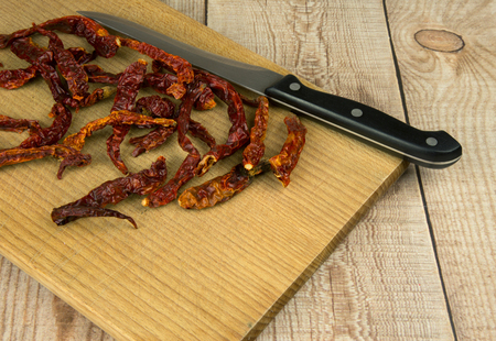 dozen: A dozen of dried chili peppers and a kitchen knife on an old wooden chopping board. Horizontal top view