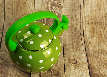stovetop: Metal, traditional kettle with a double bottom, water, whistle, green with white dots on a wooden countertop.Horizontal view on top.